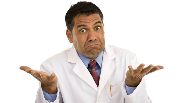 Puzzled male shrugging wearing lab coat